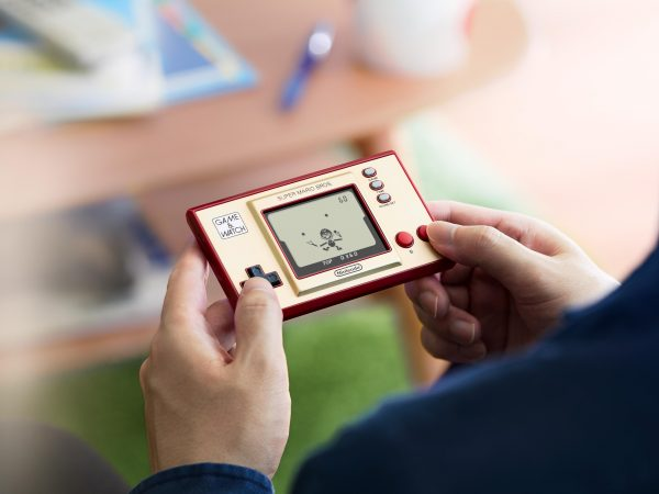Someone playing the Game & Watch: Super Mario Bros.